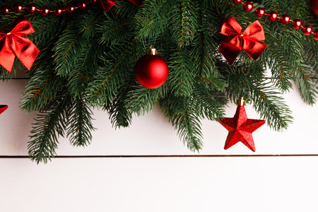 Christmas tree decoration frame on wooden background, fir tree branch, red baubles