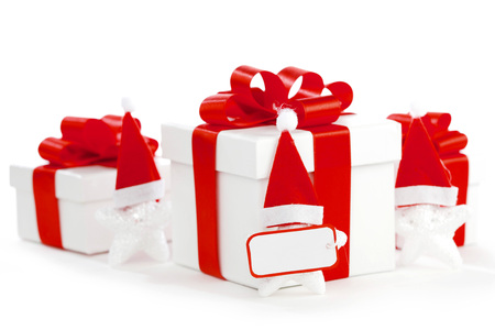 White gift boxes with red ribbons, stars with santa claus hats isolated on white background