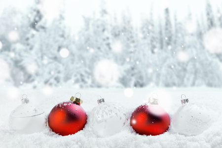Merry Christmas and Happy New Year greeting card with balls in a row and falling snow . Background with copy space .