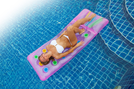 Enjoying suntan. Vacation concept. Top view of slim young woman in bikini on the pink air mattress in the swimming pool. Stok Fotoğraf