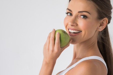 Young woman with healthy teeth smiling and biting green apple