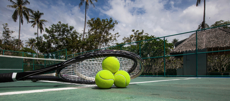 Tennis balls and racket in outdoor tropical court