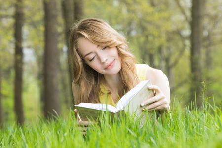 Pretty girl laying on the grass and reading a book in spring park and smiling