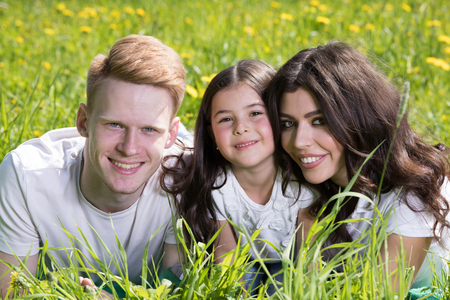 Happy smiling family laying on the grass in the park