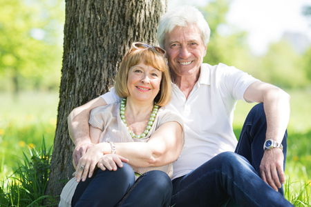 Happy senior couple in the park in summer day sitting under tree