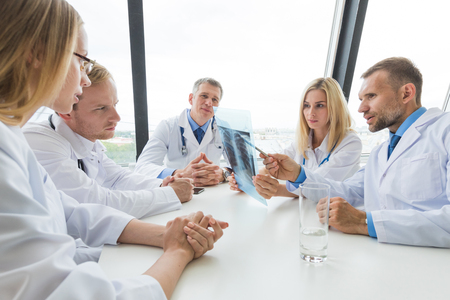 medical colleagues discuss x-ray sitting at the office table