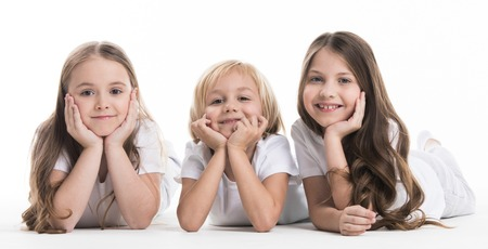 Three happy children laying on floor resting head on hands isolated on white background Stok Fotoğraf