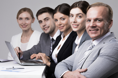 Business people sitting in a row and working together with laptop and documents