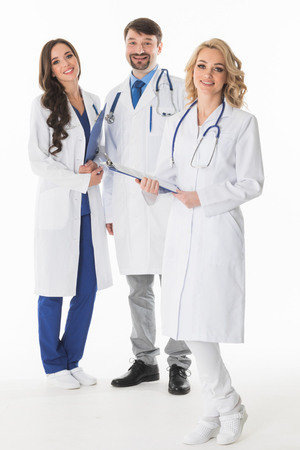 Successful team of medical doctors are looking at camera and smiling , studio isolated on white background Stok Fotoğraf