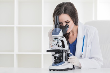 Young scientist with microscope in a laboratory doing some research