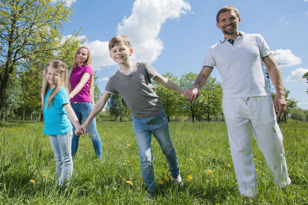 Happy young family of couple and two children spending time in summer park Stok Fotoğraf