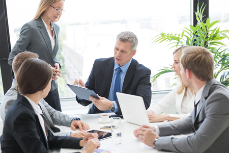 Mixed group of white collar workers at business meeting discuss documents, Business man reading contract at office table Stok Fotoğraf