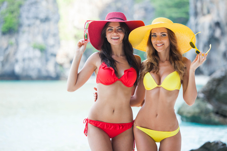 Two beautiful female friends in bikini and sunhats on beach, blonde and brunette, long hair, perfect sports figures, trendy red and yellow swimsuits, sunglasses, relaxation on a tropical island, summer