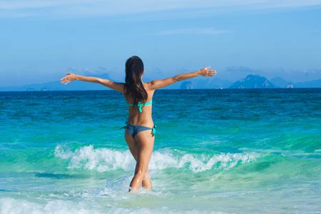 Piękna szczęśliwa dziewczyna idzie do tropikalnego morza z podniesionymi rękami