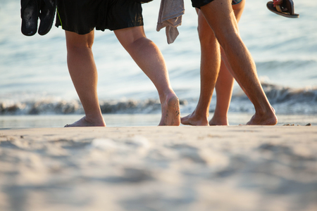 Summer holidays, travel concept - close up of people legs walking on beach st sunset