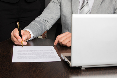 Close up photo of businessman sitting at office desk in front of laptop and singing contract document Stok Fotoğraf