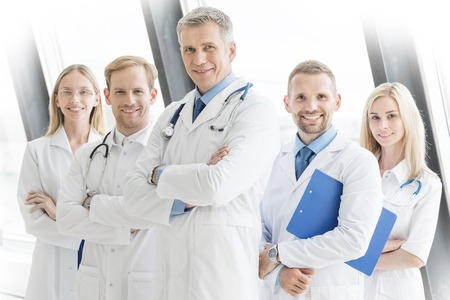 Successful team of medical doctors are looking at camera and smiling while standing with arms crossed in hospital