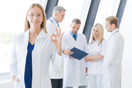 Female doctor showing Ok sign , team of doctors on background