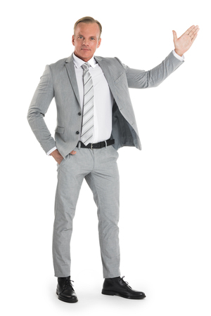 Businessman pointing with hand palm at empty copy space, studio isolated on white background, full length portrait Stok Fotoğraf