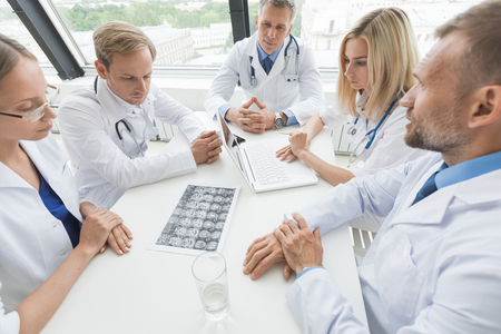 Team of doctors discuss brain scan sitting around the table