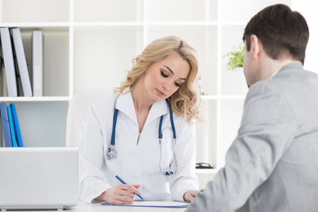 Doctor with patient reading a contract document in clinical office or writing prescription