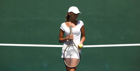 Female tennis player in white at resort court