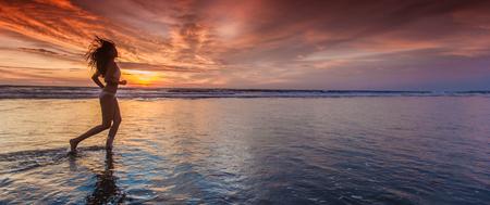 Beautiful sporty girl in bikini run on the seashore at sunset