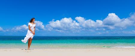 Woman in white dress walking in tropical sea beach enjoying wind Stok Fotoğraf