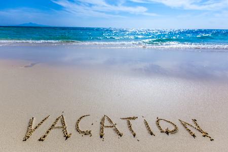 Vacation word writing on tropical sea beach