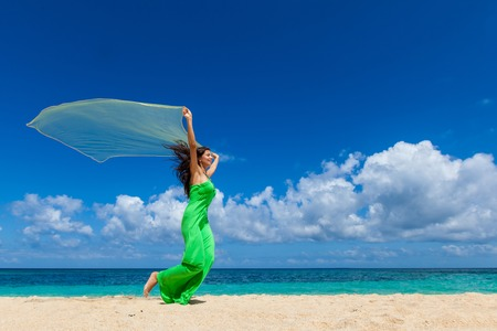 Young beautiful woman in dress run on beach holding fabric