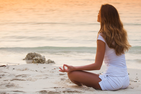 Young healthy woman practicing yoga on the beach at sunset Stok Fotoğraf