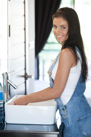 Side view of beautiful young woman in bathroom washing hands Stok Fotoğraf