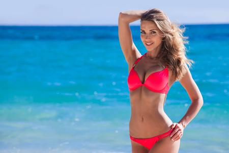 Hübsches lächelndes Mädchen im Bikini am tropischen Meeresstrand