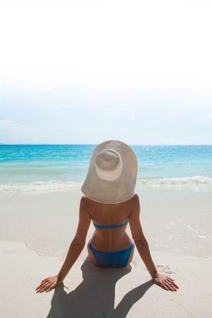 Woman in bikini and sunhat sitting on beach and looking at sea Stock Photo