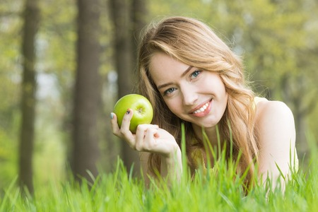 Blonde pretty girl laying on the grass in spring park and smiling holding fresh green apple