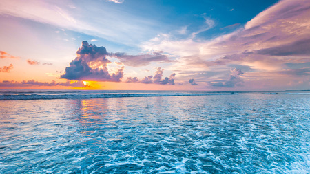 Verbazingwekkende kleurrijke zonsondergang boven zee van Bali strand en majestueuze cloudscape