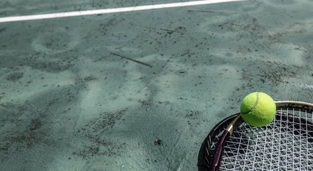 Tennis ball and racket in outdoor tropical court
