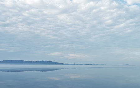 Early morning landscape with calm lake and forest under heavy cloudcover