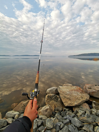 Fishing on the lake in morning, view on hand holding fishing rod