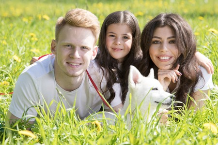 Happy smiling family of parents and daughter with pet dog in the park