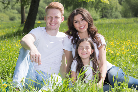 Portrait of happy smiling family of parents and girl sitting on grass with dandelion flowers at sunny summer day Imagens