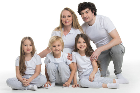 Studio portrait of family in white clothes with three children isolated on white background