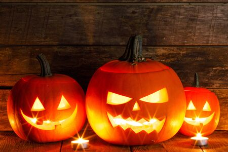 Halloween pumpkin heads jack o lantern and candles on wooden background Imagens
