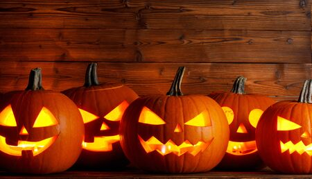 Glowing Halloween pumpkins head jack o lantern on wooden background