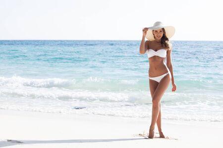 Woman in bikini and sunhat on the beach