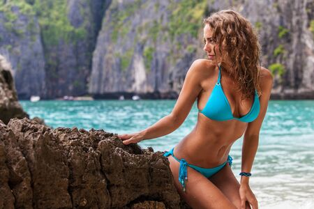 Beautiful woman in bikini posing on thai beach sitting on rocks