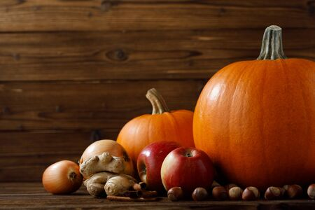 Autumn harvest still life with pumpkins, apples, hazelnut, ginger, onion and cinnamon on wooden background Imagens