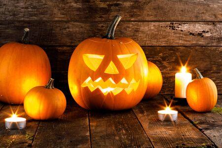 Halloween Kürbiskopf Jack o Laterne und Kerzen auf hölzernem Hintergrund