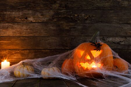 Jack O Lantern Halloween pumpkin, spiders on web and burning candles