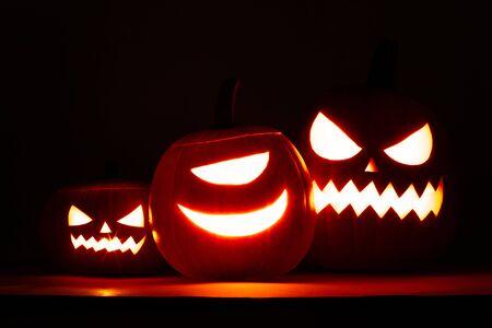 Group of Halloween pumpkin heads jack o lantern on dark background